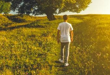 Man walking in bright field