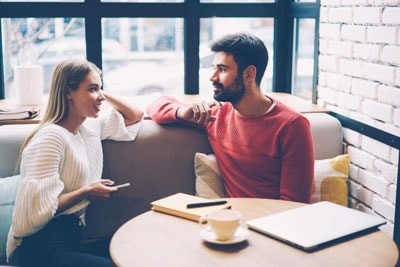 Young attractive couple talking in cafe