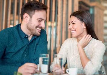 Smiling brunette couple having coffee
