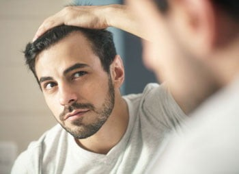A man reviewing his haircut in the mirror