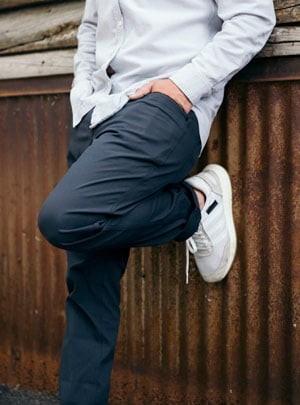 Man bending his knee leaning against wall wearing AT Slim pants