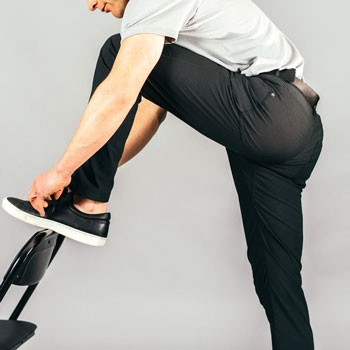 Man stretching to tie shoot wearing Western Rise Evolution pants