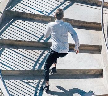 Man running upstairs in Western Rise shirt