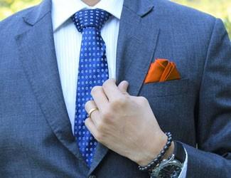 Man wearing blue suit and orange pocket square