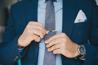 Man with pocket square adding a tie clip
