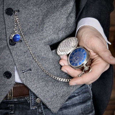 A man checking a pocket watch with a blue watch face