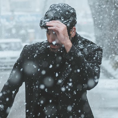 Man pulling newsboy cap down over eyes in snow