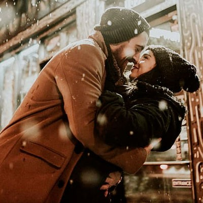 Man and woman wearing winter hats kissing