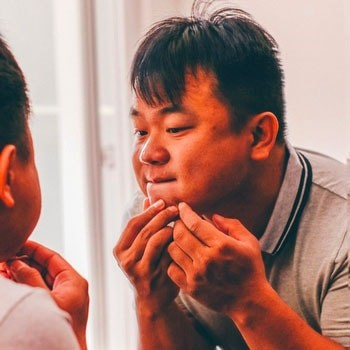 Asian man popping pimple on his chin