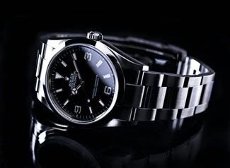 A silver Rolex watch on an all black background