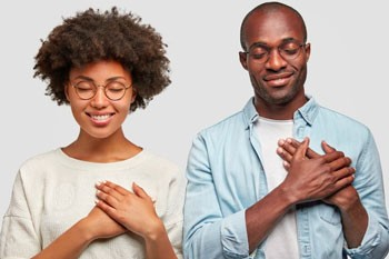 Black couple holding their hands over their hearts
