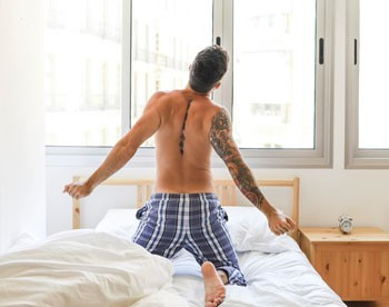 Shirtless man stretching in bed