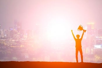 Person raising arms and trophy in success