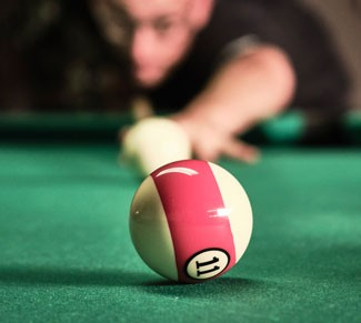 Man lines up shot on pool table