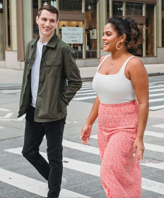 A man and woman smile while walking down the street together