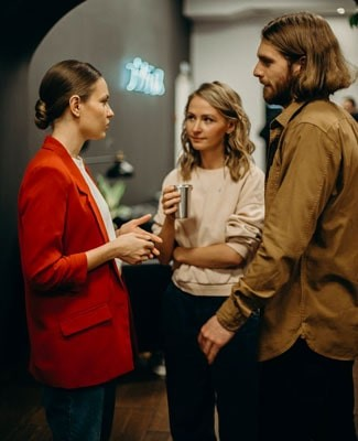 A woman listens intently as another woman and a man converse