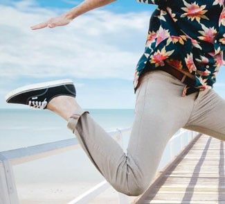 Man with rolled up pants jumping on pier