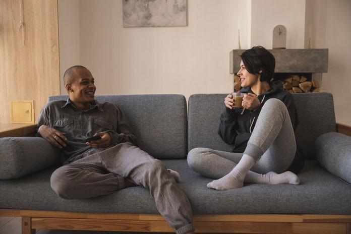 Interracial married couple talking on couch