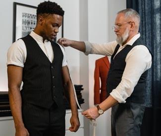 Professional clothier measuring man's arm