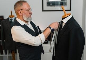 Professional clothier adjusting a custom suit