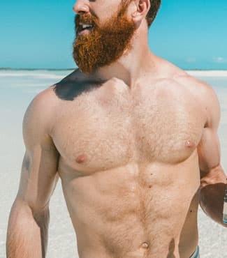 Muscular man with beard on beach