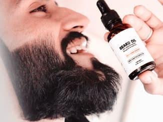 Bearded man holding bottle of beard oil