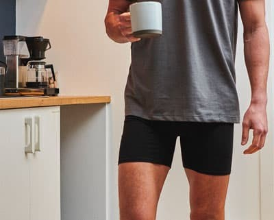 Man in boxer briefs and t-shirt holding a coffee cup