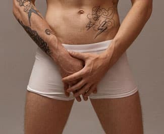 Man in white boxer briefs holding his crotch