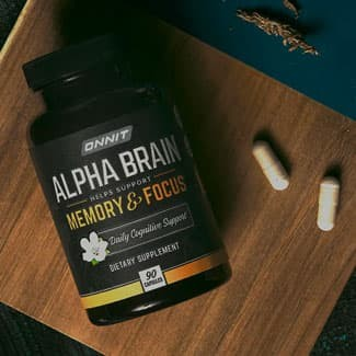 Bottle of Onnit Alpha Brain and two pills on wooden board
