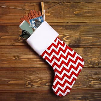 Stocking hanging against a wooden wall with gifts spilling out